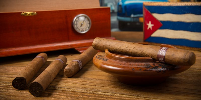 Cuban cigars and humidor with ashtray on rustic wooden table with Cuban painting of american old car in background
