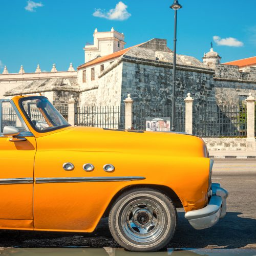 HAVANA,CUBA - APRIL 21, 2015 : Vintage american car parked next to an old colonial castle
